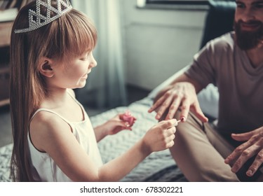 Cute little girl and her handsome bearded dad are playing in her room. Girl is painting her dad nails