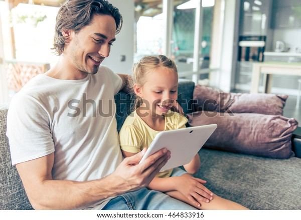 Cute little girl and her handsome father are using a digital tablet and smiling, sitting on couch at home