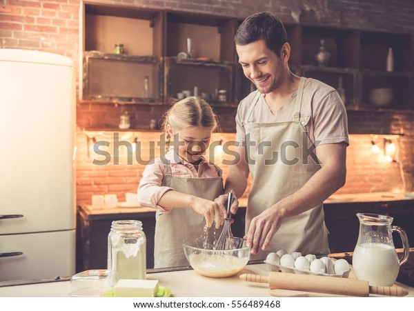 Cute little girl and her handsome dad in aprons are whisking eggs and smiling while baking in kitchen at home