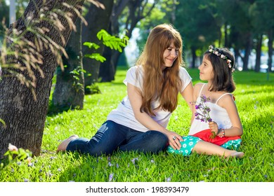 Cute little girl with her loving mother sitting barefoot on lush green spring grass in the shade of large trees smiling into each others eyes