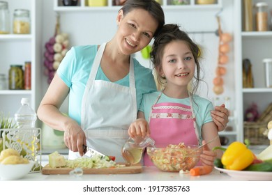 Cute little girl with her mother cooking together at kitchen table