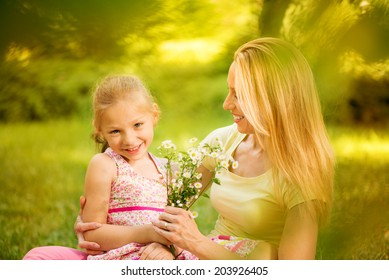 Cute little girl and her mother with bouquet flowers in the park