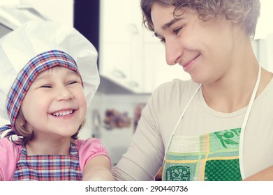 Cute little girl with her mother bake cookies at home kitchen