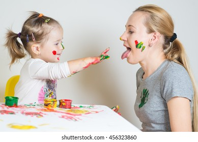 Cute little girl and her mother playing with colored paints on studio background