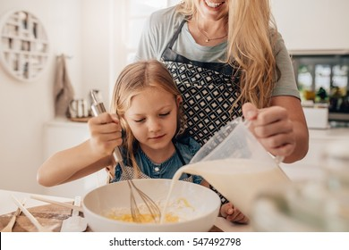 Cute little girl and her mother mixing batter in the bowl. Mother pouring milk with daughter whisking the batter.