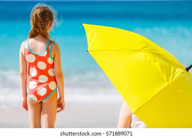 Cute little girl and her mother with big yellow umbrella hiding from sun at tropical beach