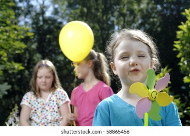 Cute little girl and her older sisters blows at colorful spinner in the garden.