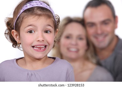 A cute little girl with her parents in the background.