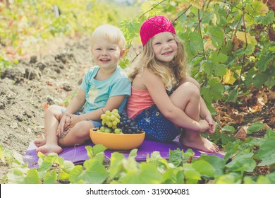 A cute little girl and her younger brother outdoor in autumn vineyard