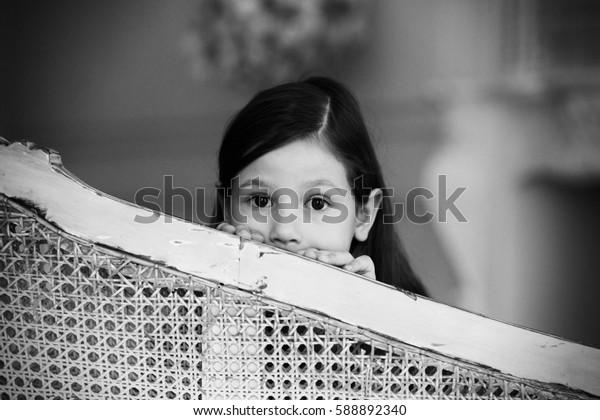 Cute little girl hiding behind a sofa, black and white photo