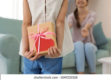 Cute little girl hiding present for mother behind her back