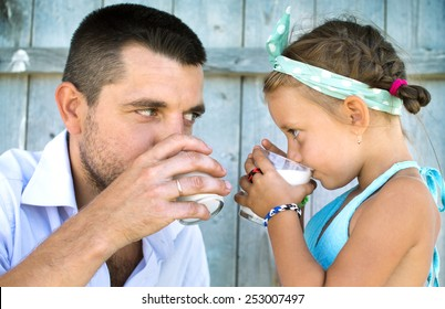 Cute little girl with his father holding glasses of milk over wooden background