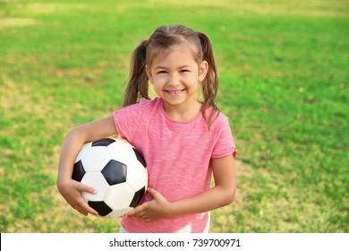 Cute little girl holding ball outdoors