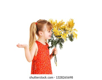 Cute little girl holding a bouquet of yellow mimosa. Concept on March 8. Little girl with bouquet flowers.