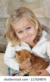 Cute little girl holding a cat. Positive feeling