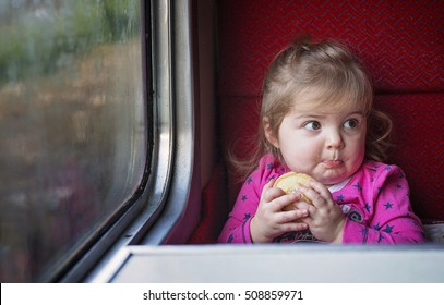 Cute little girl holding a festive mince pie next to a window on a train journey