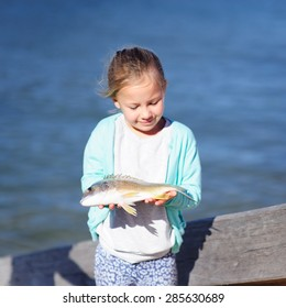 A cute little girl holding a fish with the sea water in the background, focus on the fish