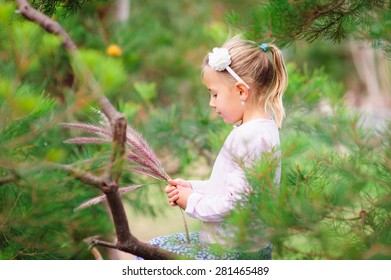 Cute little girl holding grass or flower stalks in her hands in a field or a garden on a summer day