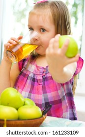 cute little girl holding green apple and drinking apple juice