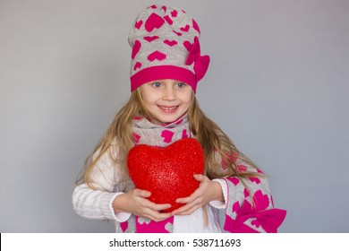 cute little girl holding a heart Valentine's Day. She is wearing a hat and scarf with hearts.