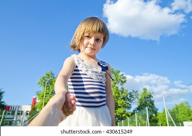Cute little girl holding her mothers hand over the blue sky. Follow me concept