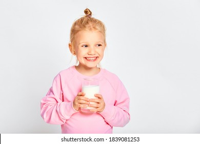 Cute little girl holding a large glass of milk. Kid 4-5 year old posing in studio on gray background
