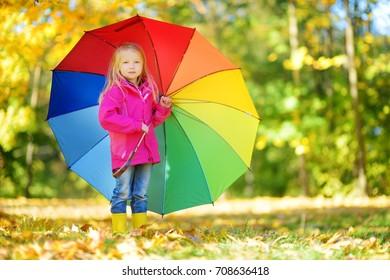 Cute little girl holding rainbow umbrella on beautiful autumn day. Happy child playing in autumn park. Kid gathering yellow fall foliage. Autumn activities for children.
