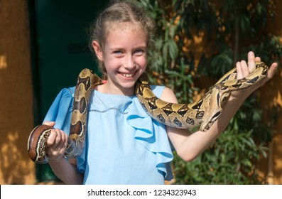 Cute little girl holding snake in her hands.