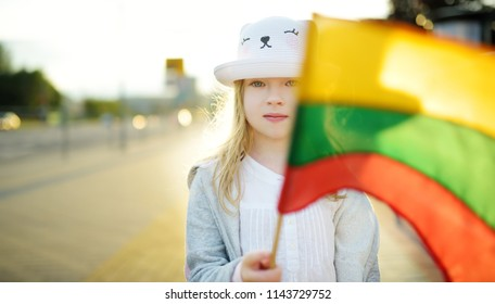 Cute little girl holding tricolor Lithuanian flag on Lithuanian Statehood Day