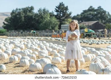 Cute little girl holding a white pumpkin on a pumpkin patch