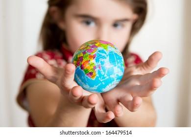 Cute little girl holding World Globe on her Hands