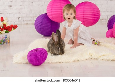 Cute little girl holds basket with flowers and easter rabbit