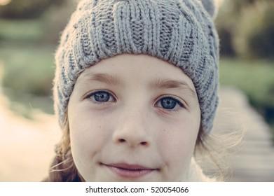 Cute little girl with honest blue eyes in bear hat