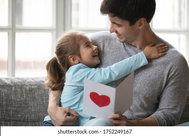 Cute little girl hug cuddle happy young father present handmade postcard for birthday or anniversary, smiling small daughter embrace dad greeting congratulating at home, show love and gratitude