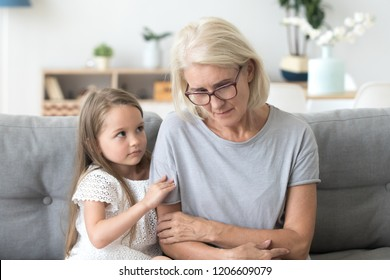 Cute little girl hug upset grandmother feel sad and down comforting her, small granddaughter embrace grandma caressing showing empathy and love, grandchild make peace with granny asking forgiveness