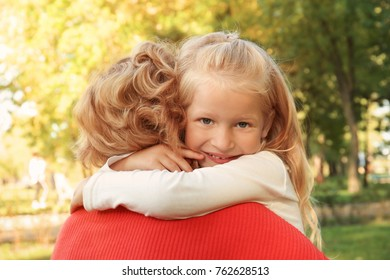 Cute little girl hugging grandmother in park