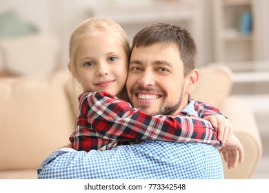 Cute little girl hugging her father at home