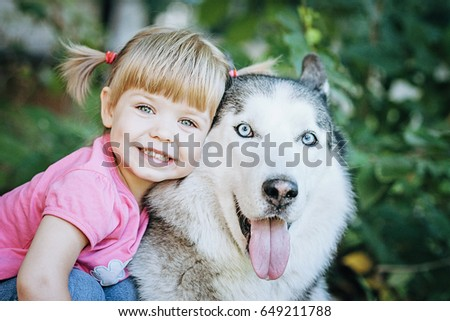 Cute little girl hugging a husky dog in park. Good sunny weather,bright sunlight and cute models. Dog heavy breathing with pink tongue hanging out