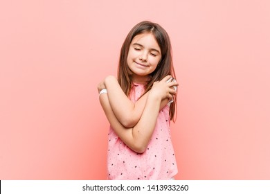 Cute little girl hugs himself, smiling carefree and happy.