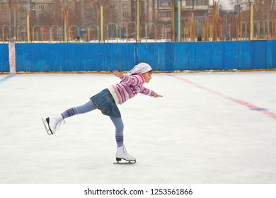 cute little girl ice skating. child winter outdoors on ice rink