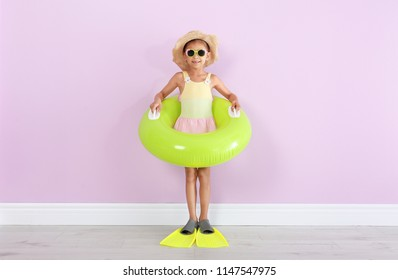 Cute little girl with inflatable ring wearing flippers near color wall