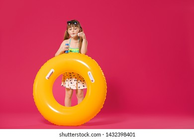 Cute little girl with inflatable ring blowing soap bubbles on color background
