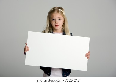 Cute little girl isolated on neutral background holding sign