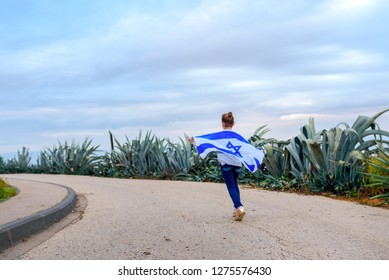 Cute little girl with Israeli flag running in the road on sky cloud and plant background. Concept Israel run to election, marathon, winter weather, race calendar. Copy space for text.