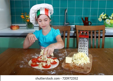 Cute little girl in Italian chief hat makes pizza with tomatoes and grated cheese - cooking, food and pleasure concept