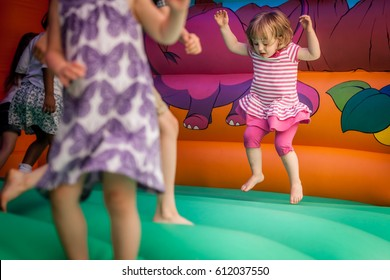 Cute little girl jumping inside the inflatable bouncy castle