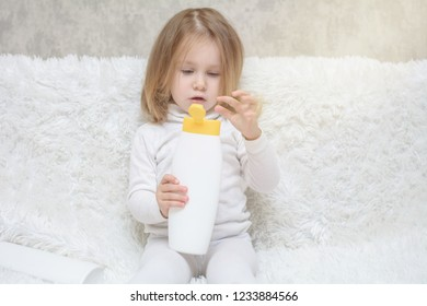 Cute little girl keeping white plastic shampoo bottle in her hands, looking at the camera. Baby bath, hygiene accessories. Cosmetic package collection for foams, shampoo