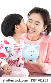 Cute little girl is kissing her young mother holding a piggy bank