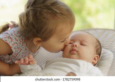Cute little girl kissing his newborn sister. Toddler kid meeting new born sibling. Infant sleeping in white bouncer under a blanket. Kids playing and bonding. Children with small age difference.