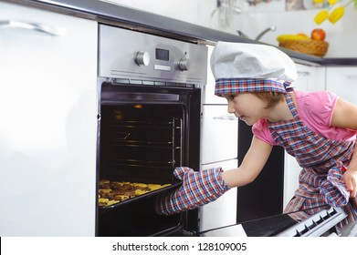 Cute little girl in kitchen mitten put cookies in stove